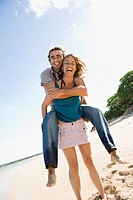 Mid_adult Caucasian woman giving man piggyback ride on beach