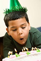 Hispanic boy wearing party hat blowing out candles on birthday cake
