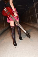 Caucasian young adult female walking with electric guitar in skywalk