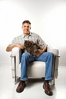 Mid-adult Caucasian man sitting holding Persian cat.