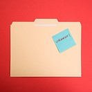 Folder with a sticky note attached reading urgent on a red background