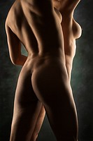Back view of nude Hispanic and Caucasian women standing together