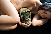 Nude Caucasian young adult woman lying down holding human skull