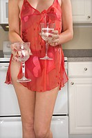 Caucasian young woman in sheer sexy red lingerie standing in kitchen holding two drinks