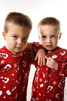 Caucasian male twin children leaning on eachother