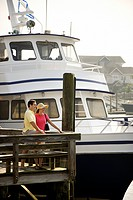Mid_adult Caucasian couple at dock with boat in background