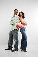 Studio shot of multi_ethnic couple standing back to back with arms crossed smiling and holding valentine heart