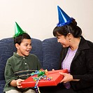 Mother giving present to surprised son at birthday party