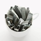 Many staples arranged in a coffee cup