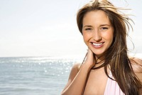 Portrait of pretty young smiling Caucasian woman with long brown hair at beach