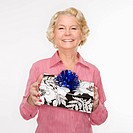 Caucasian senior woman holding present smiling at viewer