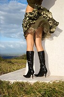 Young sexy Caucasian female standing in black boots on grassy coastline with skirt blowing in the wind