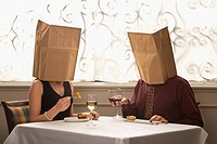 Mid adult Caucasian couple dining in a restaurant with paper bags over heads