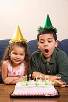 Hispanic girl and boy wearing party hats preparing to blow candles out on birthday cake