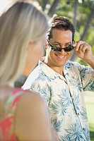 Caucasian mid adult man tilting sunglasses at woman