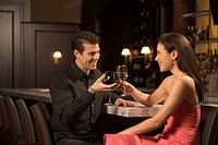 Couple at bar toasting wine glasses and smiling