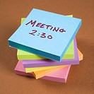 Stack of sticky notes with a meeting reminder