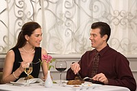Mid adult Caucasian couple smiling eating in restaurant