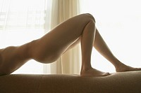 Caucasian nude woman arching in front of window