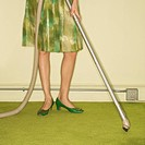 Close_up of Caucasian female legs with vacuum extension against green retro carpet