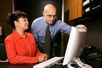 Businessman and businesswoman in office looking at computer monitor