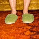 Caucasian senior female feet wearing green bedroom slippers on carpet