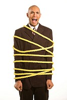 African American businessman screaming wrapped in yellow rope