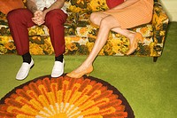 Female legs playing footsie with male legs by colorful retro sofa.