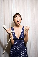 Pretty Caucasian young woman holding telephone receiver and screaming