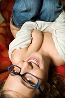 Partially nude Caucasian young adult woman lying upside down smiling and looking at viewer (thumbnail)