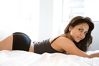 Hispanic young adult woman in lingerie lying on bed and looking at viewer