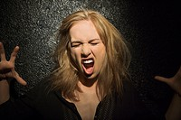 Dark portrait of sexy Caucasian mid_adult woman making fierce roaring expression