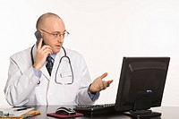 Caucasian mid adult male physician sitting at desk with laptop computer talking on cellphone