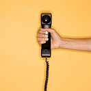 Close up of woman holding telephone receiver on yellow background (thumbnail)