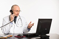 Caucasian mid adult male physician sitting at desk with laptop computer talking on telephone
