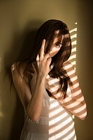 Portrait of pretty Caucasian young woman standing against wall giving middle finger