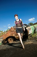 Sexy tattooed woman walking towards viewer seductively in junkyard
