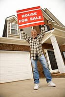 Portrait of middle_aged African_American male outside house holding up for sale sign