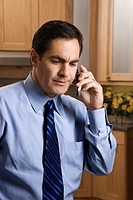 Mid_adult Caucasian male with a serious expression holding a cell phone while standing in kitchen