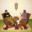 Caucasian mid_adult man and woman wearing vintage clothing seated in brown retro chairs smiling and drinking