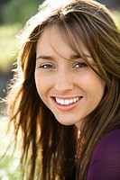 Close_up portrait of attractive young Caucasian woman with long brown hair smiling at viewer