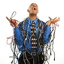 African American businessman wrapped in computer cables looking up with exasperation