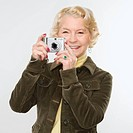 Caucasian senior woman taking photo with digital camera of viewer