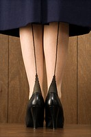 Close_up shot of Caucasian female in skirt with black heels