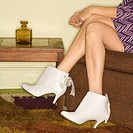 Close_up of seated Caucasian mid_adult female legs wearing white vintage boots