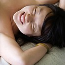 Portrait of pretty young Asian woman lying in bed smiling with eyes closed