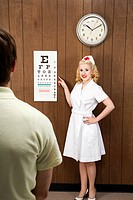 Caucasian mid_adult female nurse pointing out eye chart to mid_adult male patient