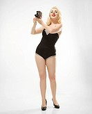 Attractive Caucasian woman wearing retro swimsuit in pinup pose with vintage camera