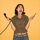 Pretty mid adult Asian woman holding telephone and cellphone with mouth open