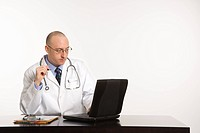 Caucasian mid adult male physician sitting at desk with laptop computer